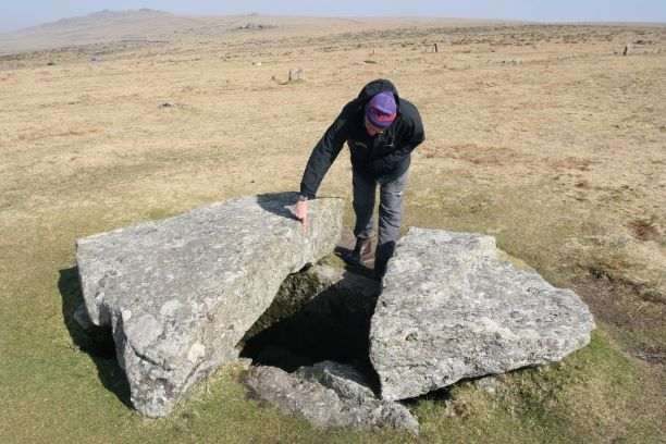 DNPA staff pointing at a broken capstone on a cist at Merrival