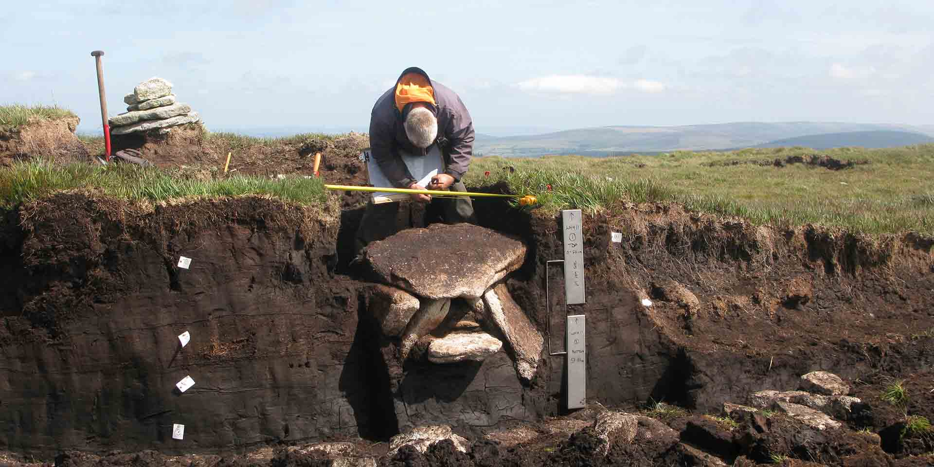 Archaeologist measuring dug-out cist at Whitehorse Hill