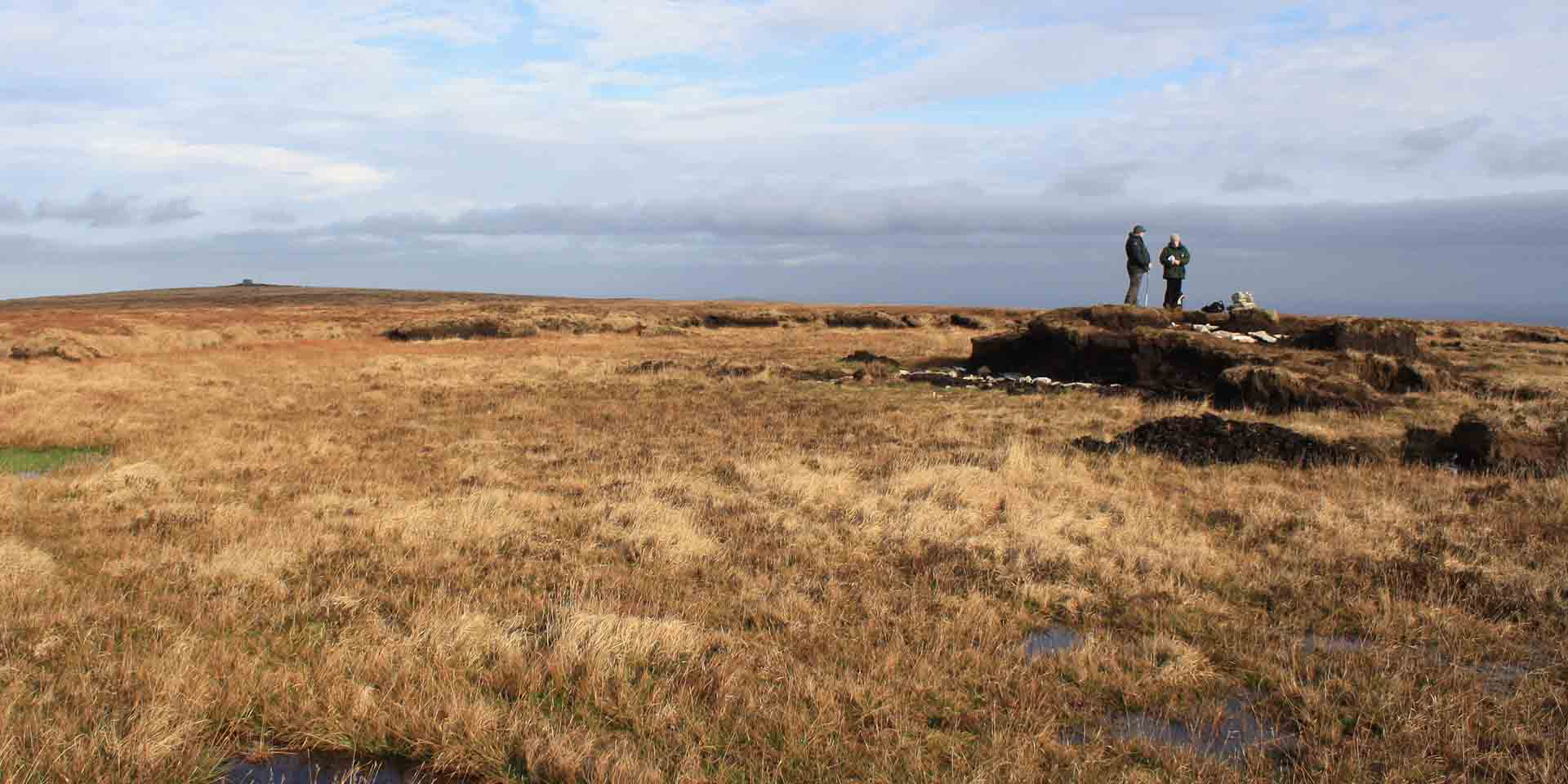 Boggy moorland and two people stood on Whitehorse Hill