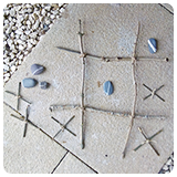 Noughts and Crosses game made out of twigs and stones