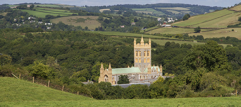 Large old abbey sticking out of rolling green hills