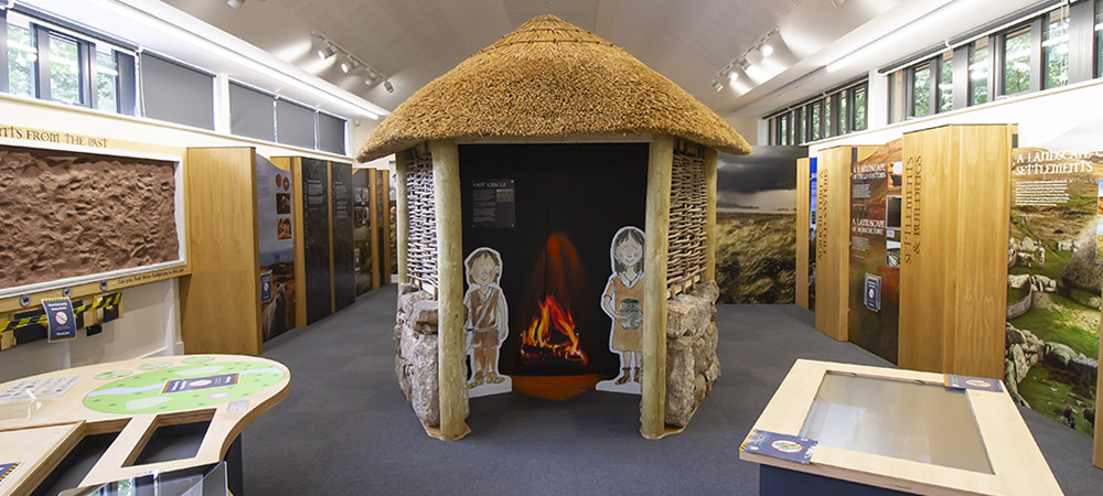 Model bronze age roundhouse with cardboard cut-out cartoon characters inside