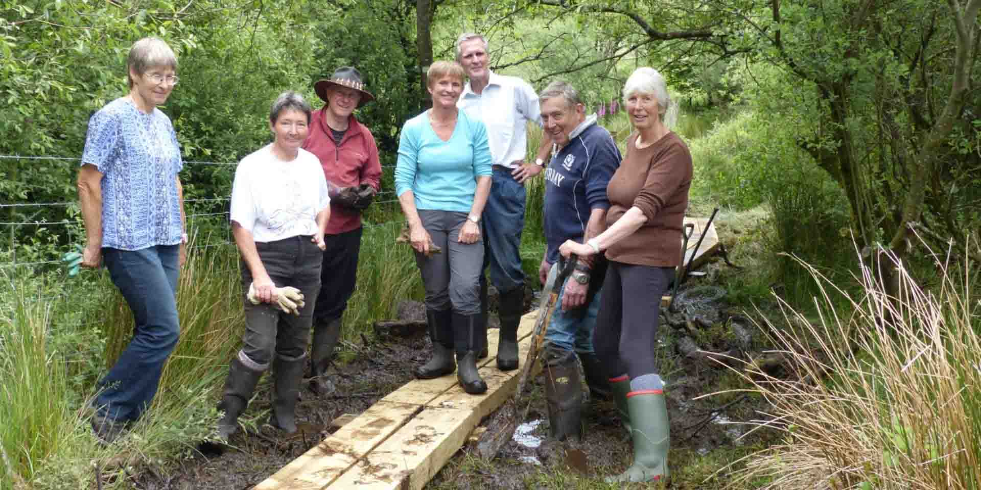 Volunteers building a boardwalk over the marshy ground