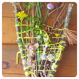 Y shaped stick wrapped in string and decorated with flowers and leaves
