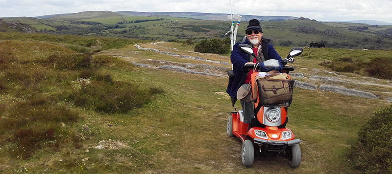 Person using mobility scooter on moorland with tramway and views in background