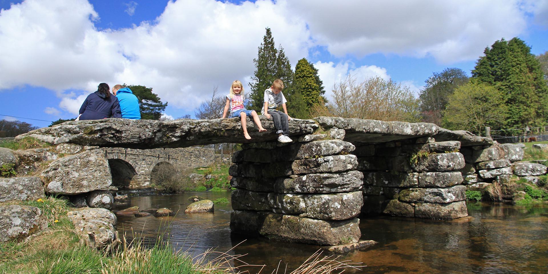 Children sat on clapper bridge at Postbridge