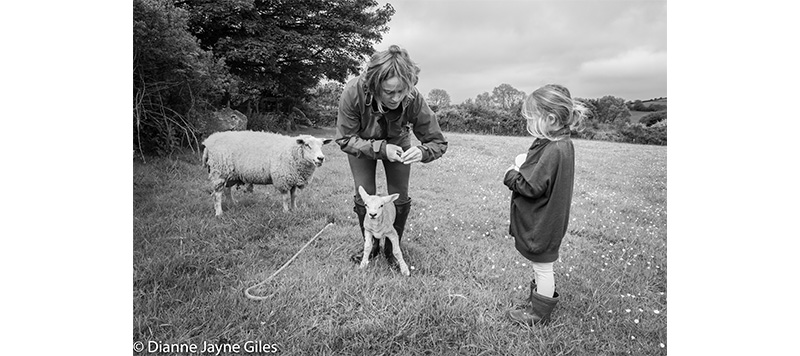 Mother and Daughter holding a lamb