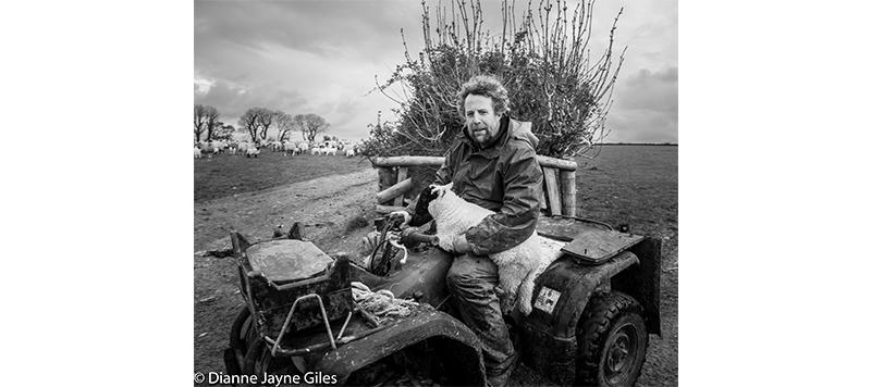Farmer Mat Cole sat on a quad bike holding a lamb