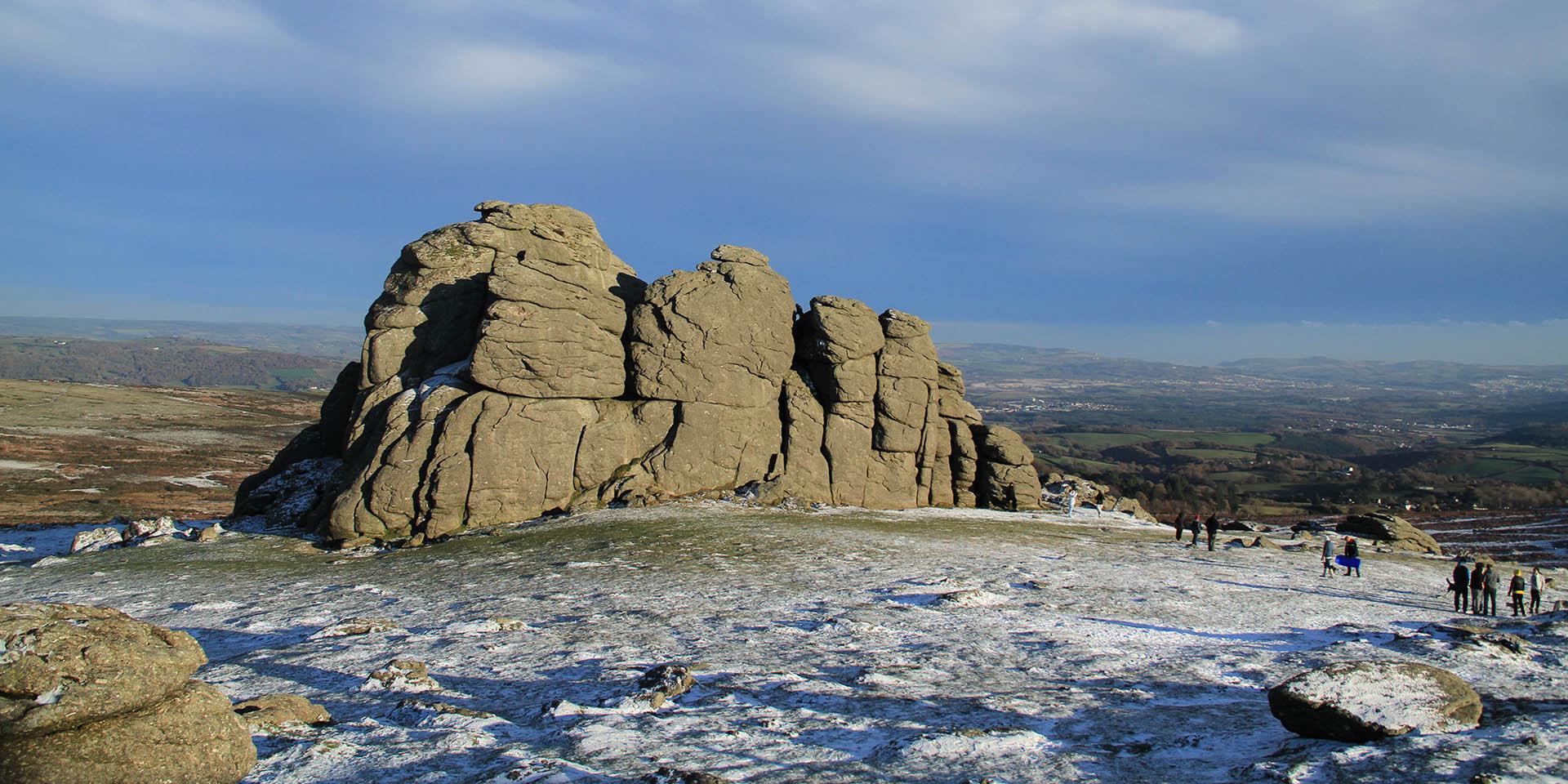 Visitors on Haytor rocks enjoying snow