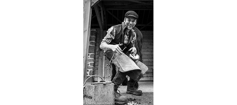 Farrier Nick working on a horse's hoof and smiling