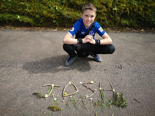 Boy smiling next to sticks and greenery spelling out 'Josh