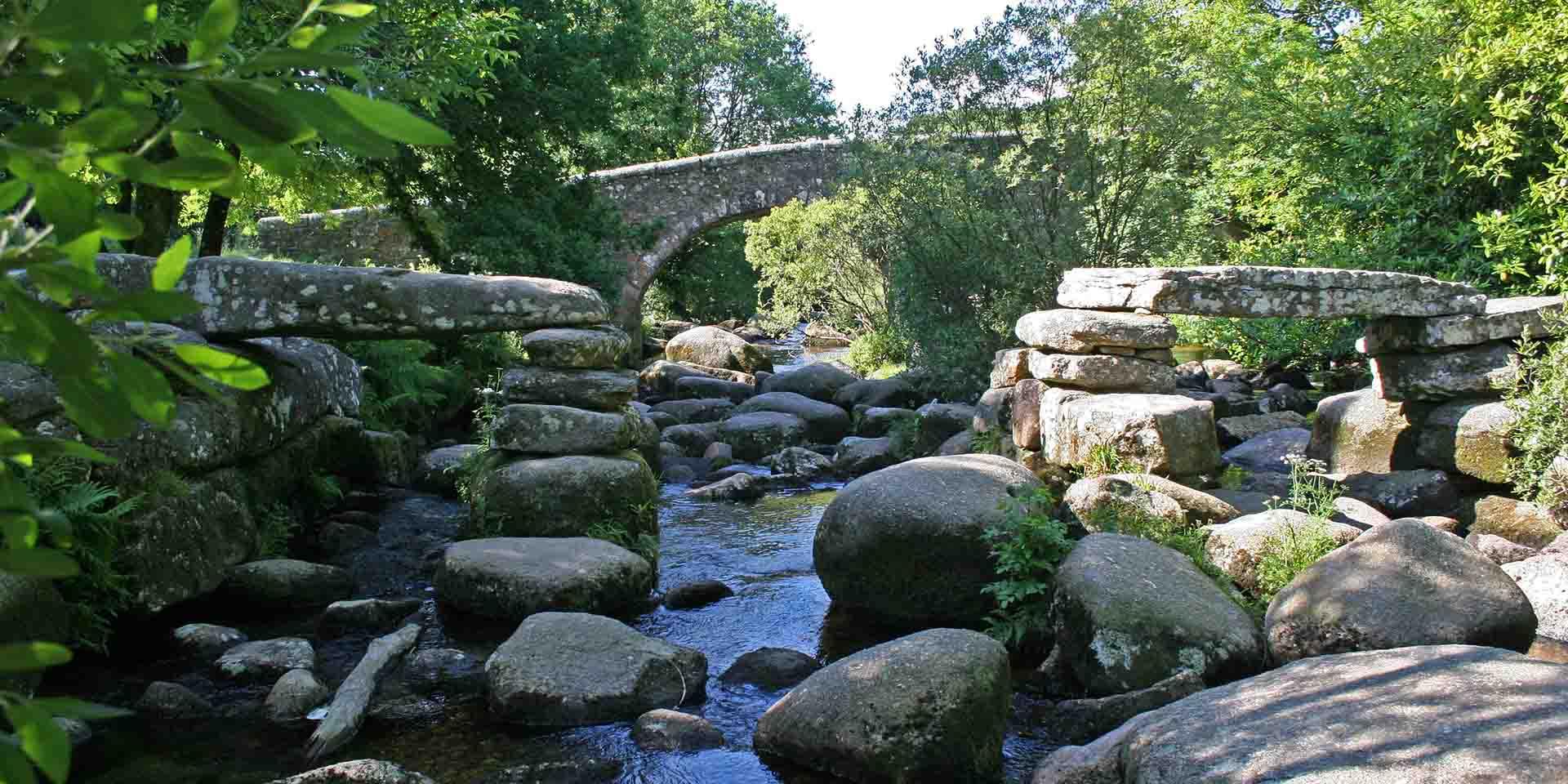 Dartmeet clapper bridge with modern bridge behind