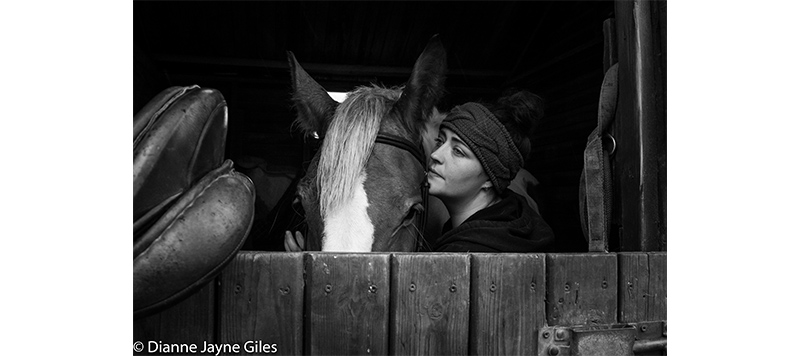 Girl in stable with her horse