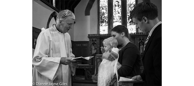 Vicar reading to baby and family at a christening