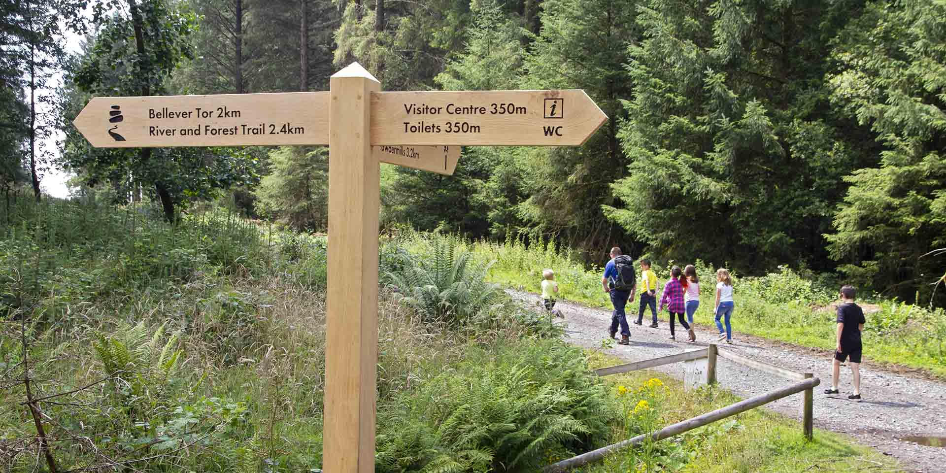 Timber signpost in forest directing to Bellever Tor and National Park Visitor Centre