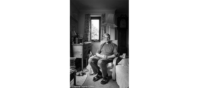 Vicar sat at home in living room