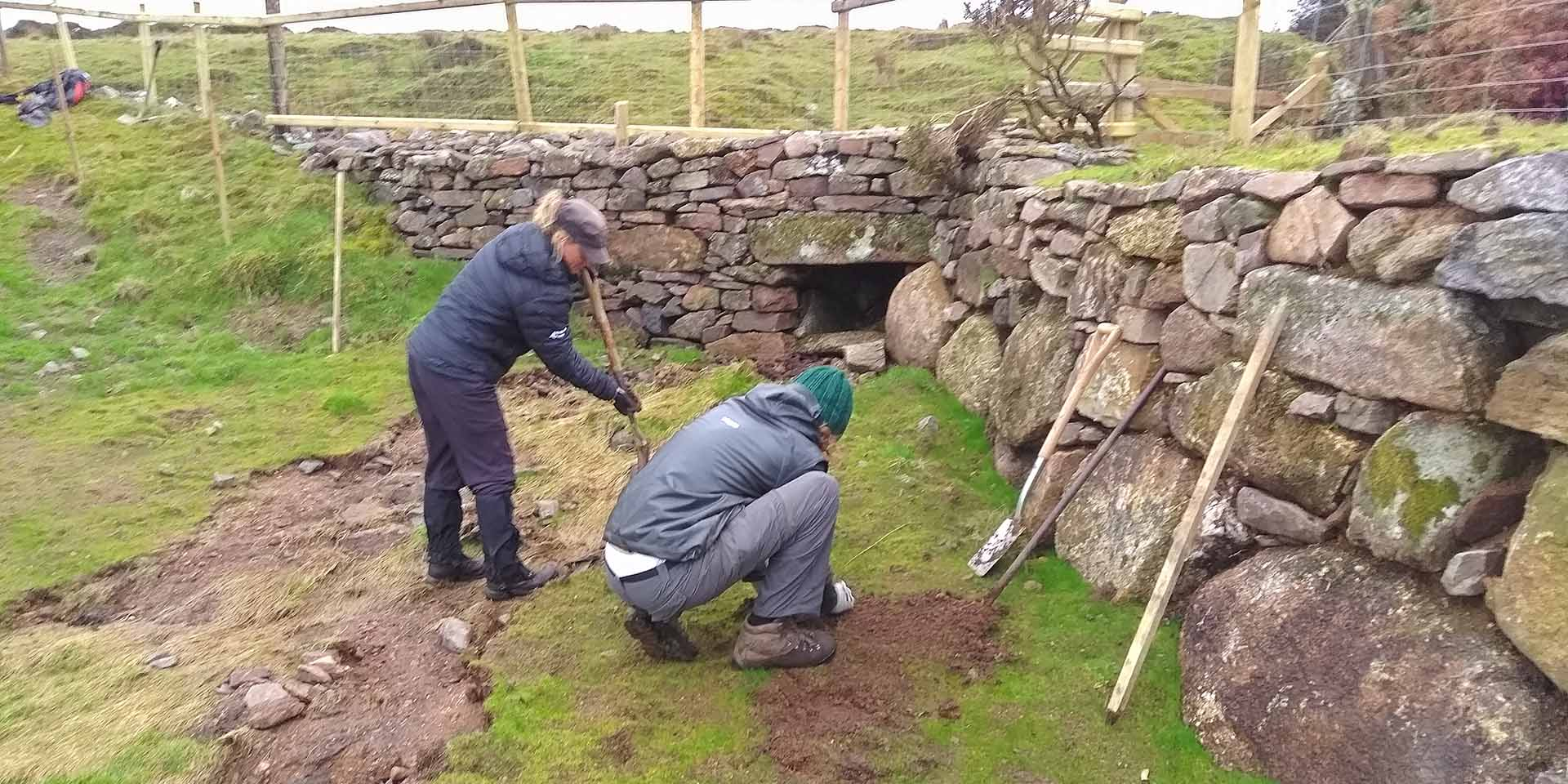 Two people repairing a stone wall
