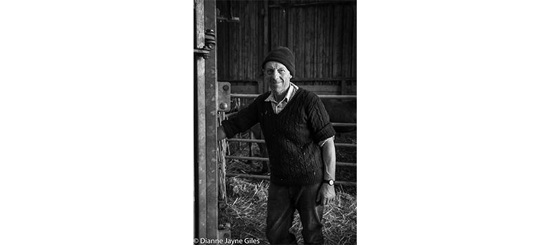 Farmer Kenny standing in a barn