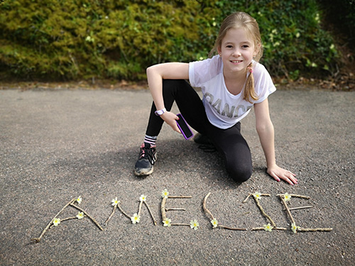 Girl smiling next to sticks and daisies spelling 'Amelie