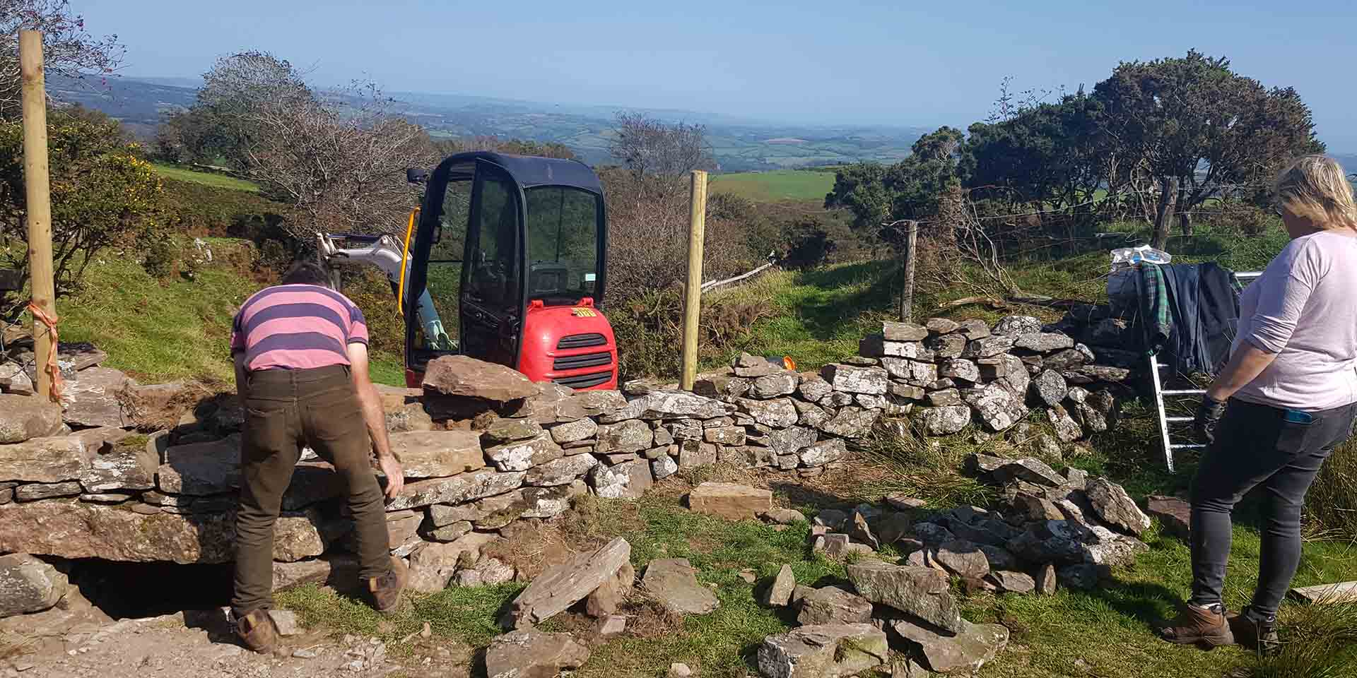 Contractors building a stone wall on moorland