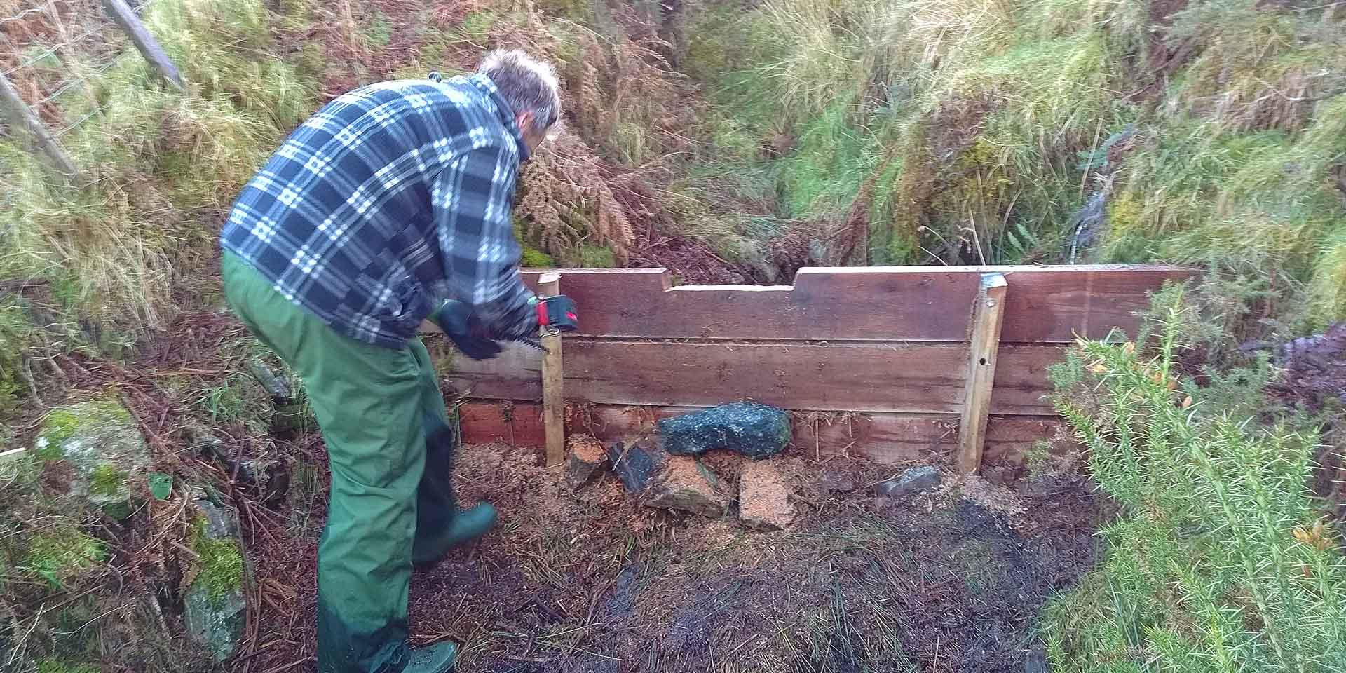 Person building a leaky dam out of timber planks