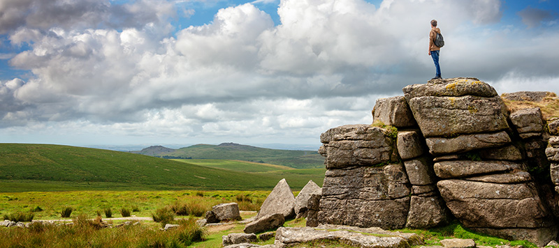 Walker stood on South Hessary Tor gazing at moorland view